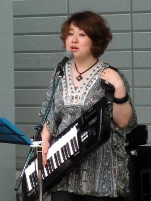 ショルダーキーボードを弾きながら熱唱する、都築ナオさん